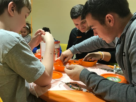 Cole Shupe, left,  works on making his Beads of Courage