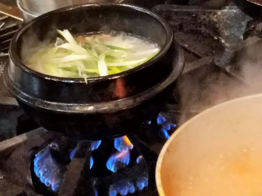 Sul Lung Tang, a silky-rich soup of beef shank, scallion and Chinese chives, cooks right in its hot stone bowl at Gangnam Korean BBQ.