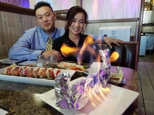 """Joseph and Young-eh Kim with a selection of their Gangnam sushi, including a lobster roll """"on fire"""" wrapped in foil and flamed with grain alcohol before serving."""
