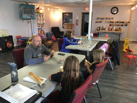 Matt Warble and his daughters play Uno at the Uprising