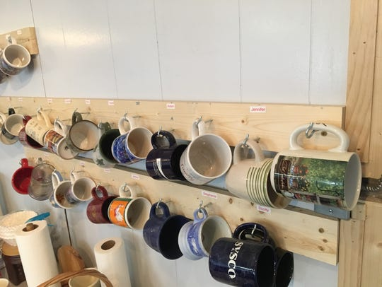 Mugs hang on the wall at the Uprising Outreach Center