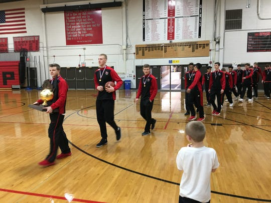 Members of the Stevens Point Area Senior High boys basketball team enter the SPASH Fieldhouse with the WIAA Division 1 championship trophy on Sunday, March 19, 2017.