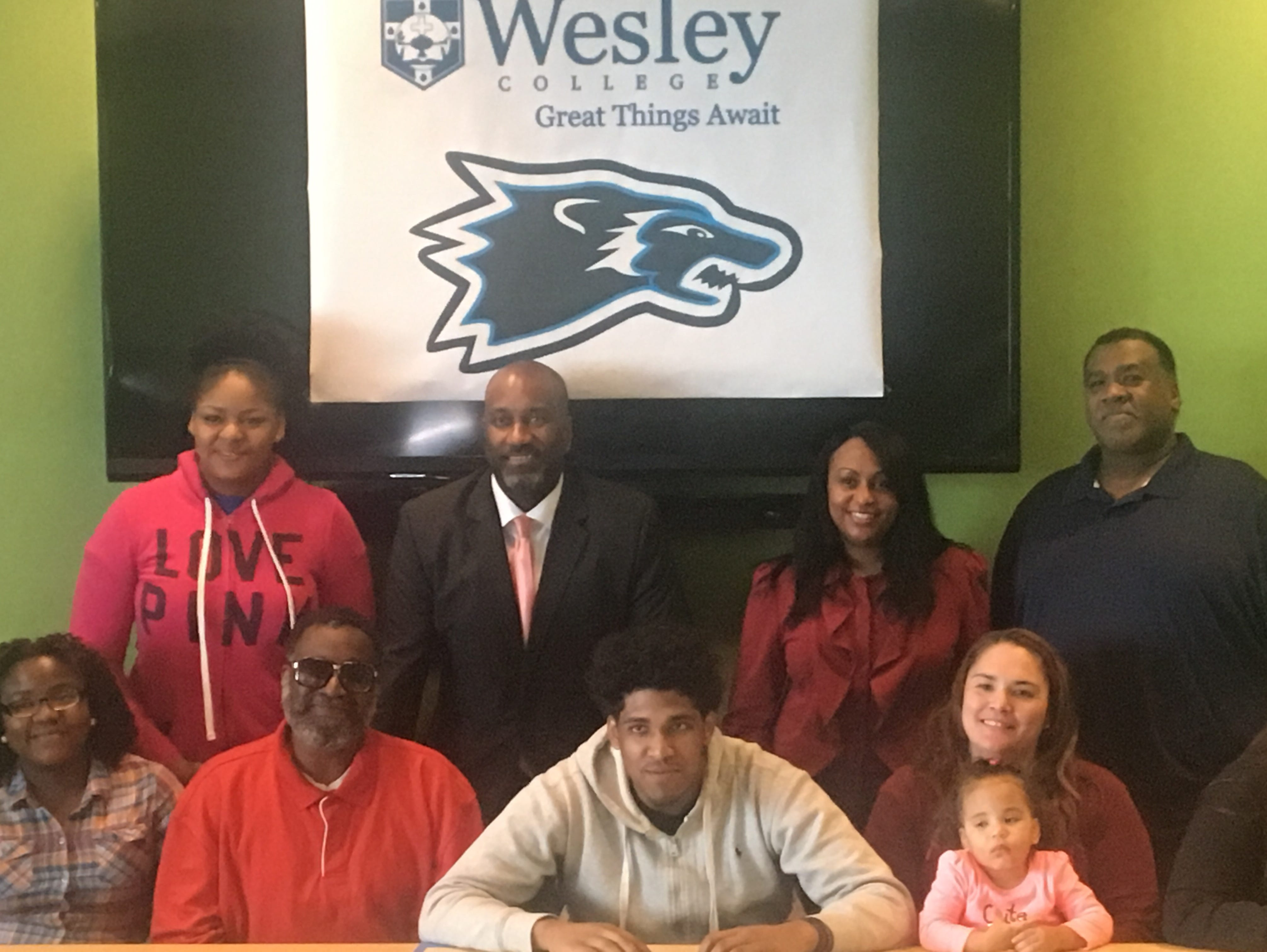 Howard High's Darin Matthews (center) is surrounded by family and friends as he commits to play football and baseball at Wesley College.