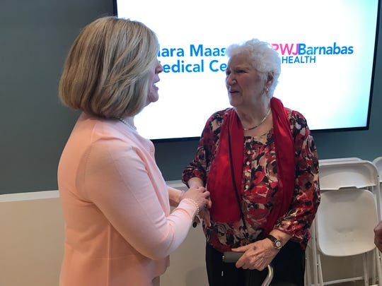 Marie Vander Zwan, 95, of Belleville, right, shakes the hand of Clara Maass Medical Center CEO Mary Ellen Clyne during an opening of the facility's new 87,000-square-foot building Monday, March 28, 2017.
