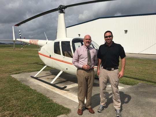Standing in front of an R44 helicopter are Andre Perez,