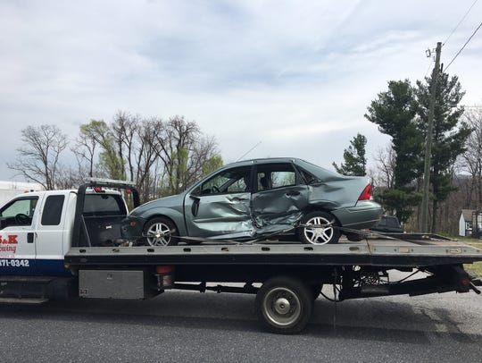 A gray Ford Focus awaits removal from the scene of