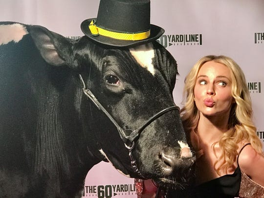"Actress Kim Crossman puckers up for a photo opp with Reaction the cow on ""The 60 Yard Line"" red carpet. The actress from New Zealand had to learn to speak with a Green Bay accent in the Packers-themed comedy filmed in Green Bay."