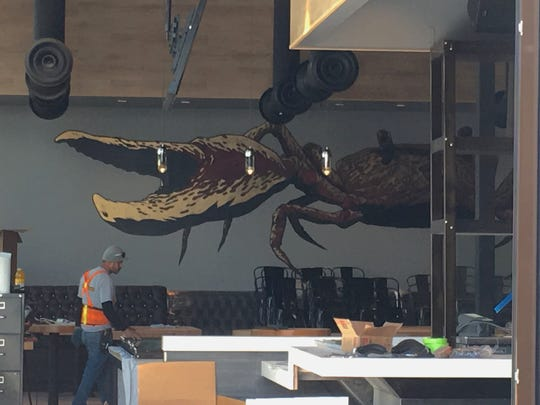 A construction worker wearing a protective brace is dwarfed by a crab mural at EMC Seafood & Raw Bar at The Collection at RiverPark in Oxnard. The restaurant will mark its grand opening with a by-reservation event on April 20.