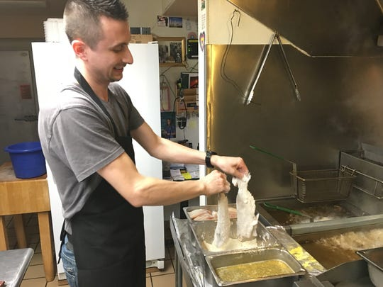 Adrian Alimi of Paradise Bar & Grill in Plover gets two catfish ready to fry.
