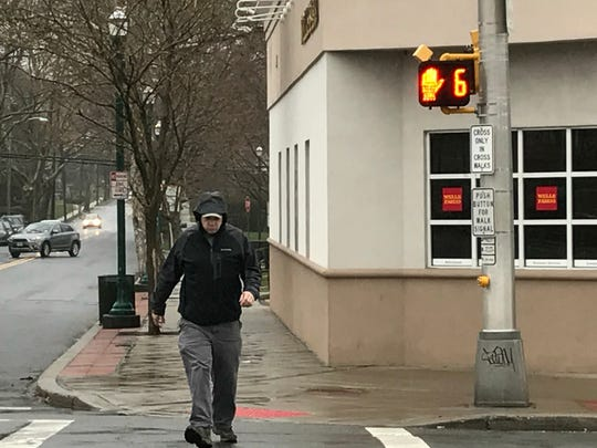 A man crossing Cedar Lane at Garrison Avenue in Teaneck. The time given to cross was lengthened in response to a pedestrian death there.