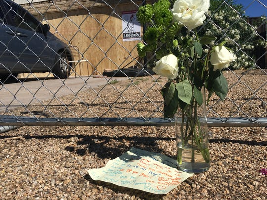 A note and a vase of white roses has been placed outside