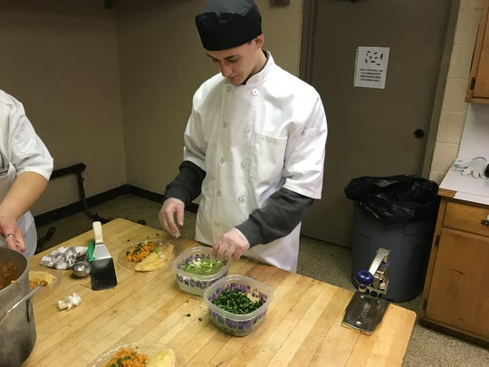 Bailey Krall, a Youth Advocate Program participant, garnishes Thursday's meal of enchiladas and Spanish rice with green onions.