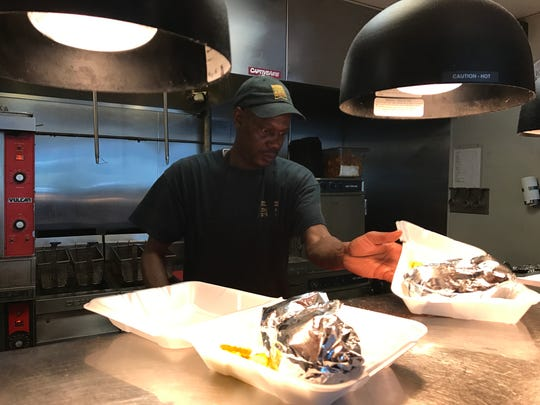 Line cook Clifford Smith preps a carryout order from