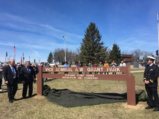Members of the family of Vice Admiral Albert Weston Grant, who grew up in Stevens Point and later commanded the Atlantic Fleet during World War I, unveil a sign at the new park in Stevens Point named for him during a ceremony on Friday, April 7, 2017.