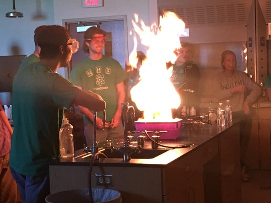 Ethan Warfield, 18, lights methane bubbles on fire during North's 8th annual science show. Warfield and his peers added dish soap to a tub of water, mixed it and added methane gas. Then they lit it on fire.
