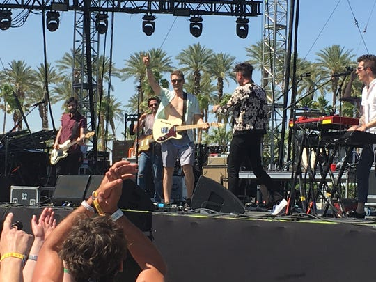 Ross Watt, a 26-year-old pulled from the crowd to play guitar during the Arkells' set Saturday at Coachella, points to the crowd.