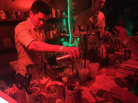 Bartenders serve up tropical drinks Sunday in the secret PDTiki bar on the Coachella grounds.