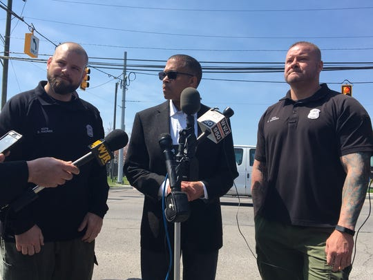 Detroit Police Chief James Craig, center, speaks about Detroit Police Officer Brian Gadwell, right, and Officer Steven Rauser at a news conference held on April 18, 2017. The officers helped rescue a pregnant woman.