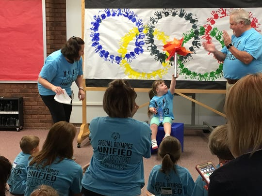 Emelia Carmack, 3, enjoys her time in the spotlight receiving a ribbon and Olympic torch after Culver Family Learning Center's Special Olympics Unified Champion Schools program.