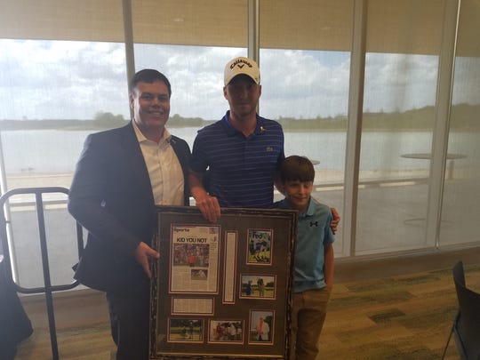 Defending FedEx-St. Jude Classic champion Daniel Berger, center, poses with tournament director Darrell Smith, left, and St. Jude patient Reid Russell.