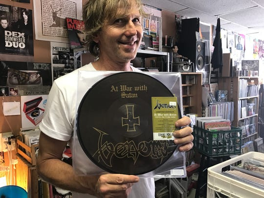 """Eric """"Elvis"""" Jones of Revolver Records shows off Venom's """"At War with Satan,'' one of the many Record Store Day releases, on Thursday, April 20, 2017."""