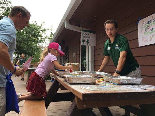 Madison Jones, 5, digs for a fossil as her father Evan Jones, left, and Kevin Sandel, a naturalist with the Conservancy of Southwest Florida, watch during the annual Earth Day festival at the nonprofit's nature center Saturday, April 22, 2017, in Naples.