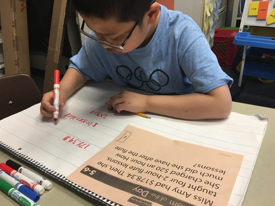 Jamin Chen works out a math word problem the old-fashioned way.
