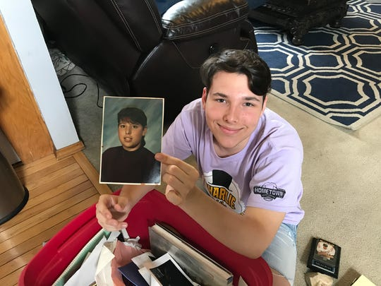 Joe Greenwood, 17, holds a childhood photo of his biological