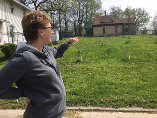 Karen Lauer points to fruit trees that have been planted