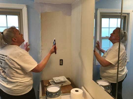 LOC Federal Credit Union volunteer Donna Martin puts down another coat in the bathroom.