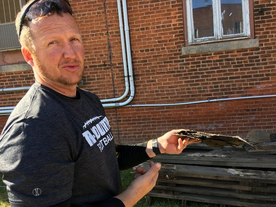 Matt Makaryk shows a piece of roofing from the Plainfield