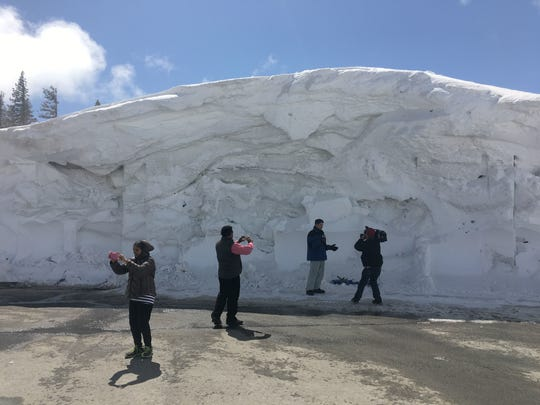 People photograph a massive snowbank at the Mt. Rose Highway summit on April 10, 2017. Snow recording devices measured record levels on Mt. Rose.