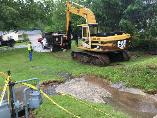 A crew from the Harrison, Arkansas, Public Works Department on Wednesday works on a homeowner's sinkhole problem.