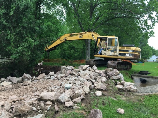 A work crew from the Harrison, Arkansas, Public Works Department puts large stones into a resident's sinkhole.