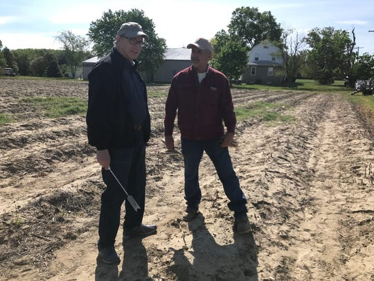 NJ Secretary of Agriculture Doug Fisher (left) holds an asparagus knife while cutting the vegetable with Fred Grasso (right) of Grasso farms and Grasso Girls Farm Market May 4, 2017.