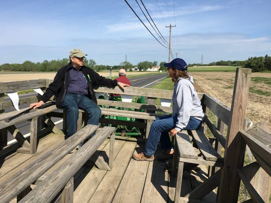 NJ Secretary of Agriculture Doug Fisher (left) rides with MaryLynn Shiles, of Grasso Girls Farm Market, to Grasso Farms' asparagus fields on Wolfert Station Road in Harrison Township. Shiles' brother Fred Grasso drives the tractor May 2, 2017.