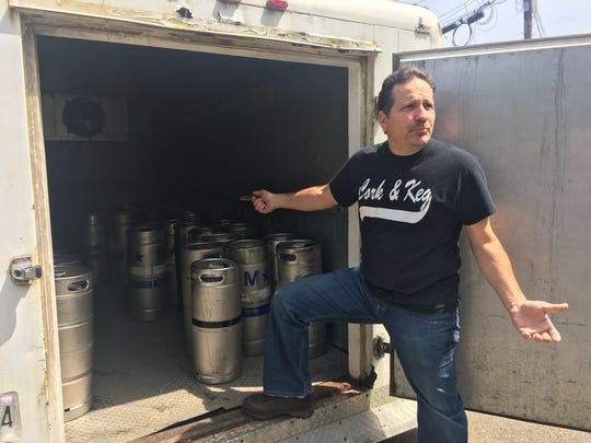 Dominick Scala, owner of Cork & Keg liquor store, stands by a refrigerated trailer that is parked outside of his business 24/7. He was issued a warning by the property maintenance official recently for this.