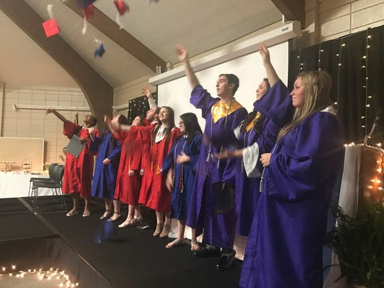 Graduates throw their caps in the air during Aiken