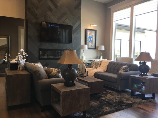 The living room featuring a 14-foot-tall ceiling and high windows overlooking an outdoor pool, at 6700 S. Colebrook Circle in Sioux Falls, a home featured in the semiannual Parade of Homes.