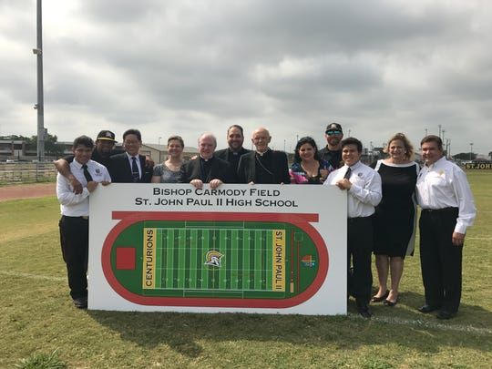 St. John Paul High School students, staff pose with a rendering of the new Bishop Carmody Football Field during a groundbreaking ceremony May 12, 2017.