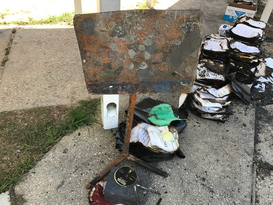 A charred music stand, CDs and triangle are pictured