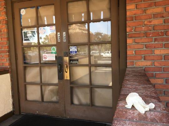 A discarded latex glove is seen outside the papered-over front doors of Chuy's Mesquite Grill in Camarillo on Tuesday. The restaurant appears to have closed Sunday or Monday in the Carmen Plaza shopping center.