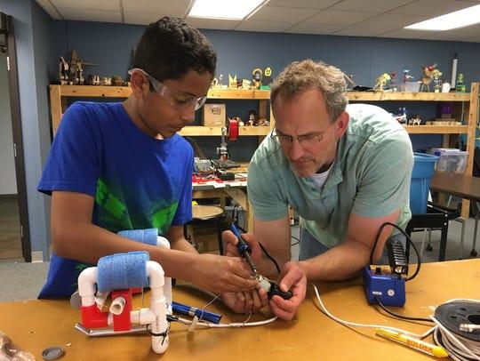 Dhruv Bansal, left, and Dennis Rockhill solder an engine