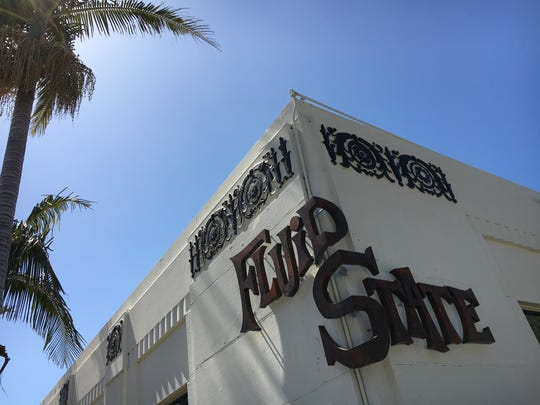 """The wrap-around sign at Fluid State Beer Garden in downtown Ventura was made by a local firm. """"Dave's Signs was the only company I talked to that would even think about it,"""" co-owner Aaron Duncan said of the piece, which is backlighted at night."""