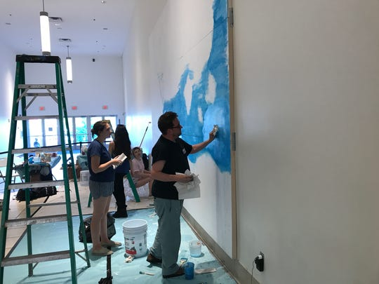 Artist Chuck Webster working with local art students on a mural at Westfield Garden State Plaza in Paramus.