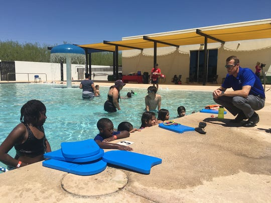 Children learn to swim while taking lessons at a Phoenix YMCA.