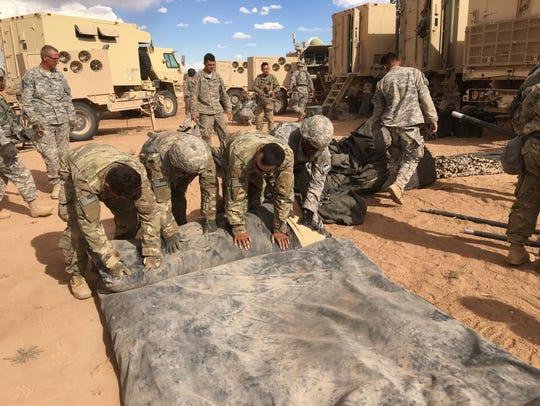 Soldiers break down and roll up a command post tent