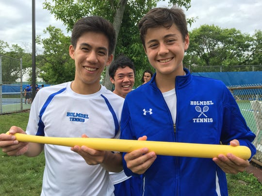 Harrison Lin (left) and Justin Wain (right) hold the Whiffle ball bat that has become part of Holmdel tennis tradition.