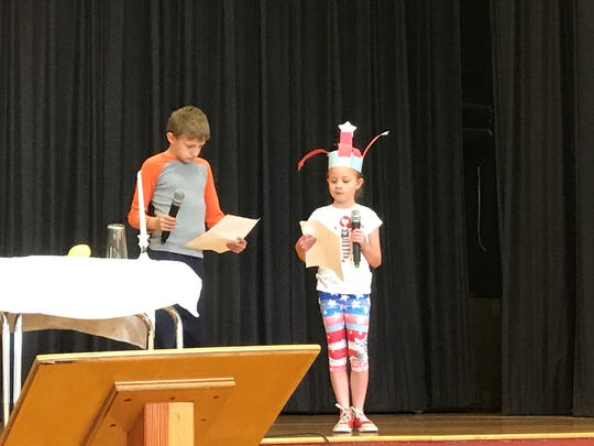 Students at the Washington  Elementary School participate in the School's Memorial Day assembly. Here two first graders stand next to the symbolic white table.