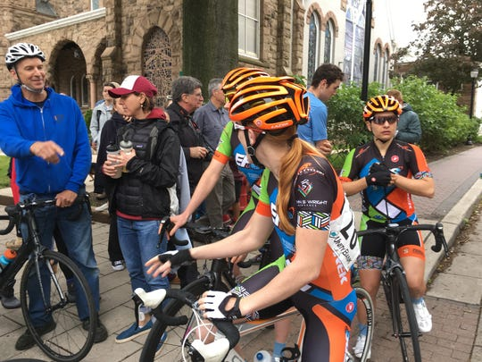 Women competitors wait to cross Main Street and enter the starting line for the Mildren Kugler Race at the Tour of Somerville on Memorial Day 2017/